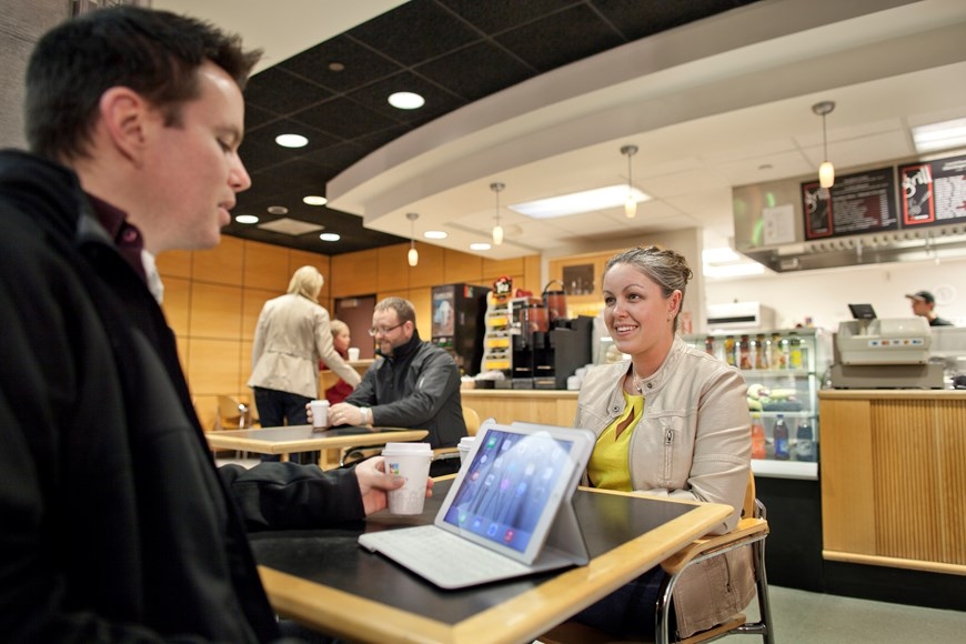 Couple sitting at a table with coffee cups and their IPAD inside the terminal